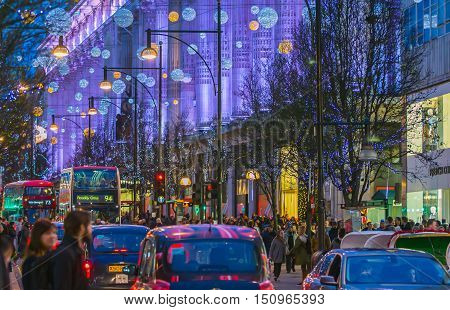 LONDON, UK - DECEMBER 30, 2015: Christmas lights decoration at Oxford street and lots of people walking during the Christmas sale, public transport, buses and taxi