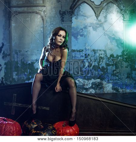 Young and sexy woman in the image of the witches in a cemetery sitting on the lid of the coffin. Vampires and zombies