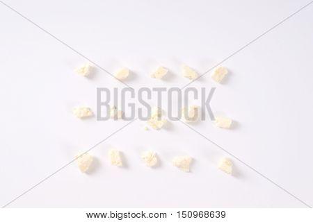 crumbles of feta cheese arranged on white background