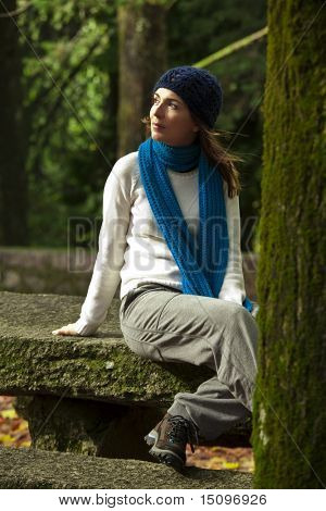 Outdoor portrait of a beautiful young woman sitting on a stone wall