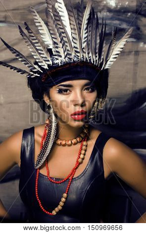 young pretty woman with make up like red indian, futher in hair, fashion hallowen concept creative