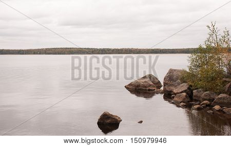 Autumn landscape rocks protruding from the lake. Sticking out of the water stones
