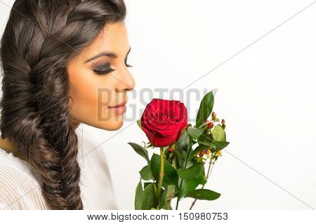 Beautiful young woman with long braided hair holding red rose
