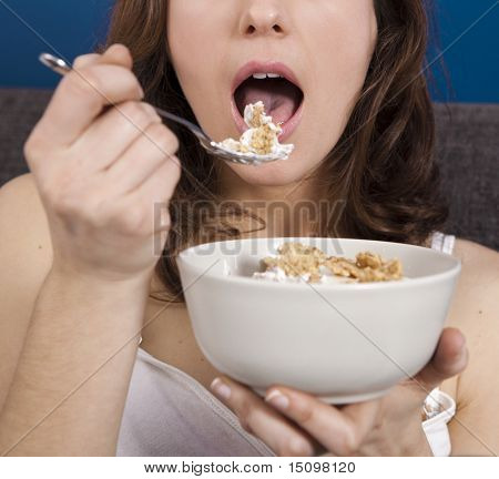 Beautiful and healthy young woman eating a cup of cereals with yogurt