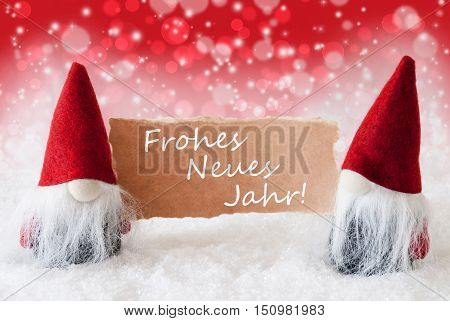 Christmas Greeting Card With Two Red Gnomes. Sparkling Bokeh And Christmassy Background With Snow. German Text Frohes Neues Jahr Means Happy New Year