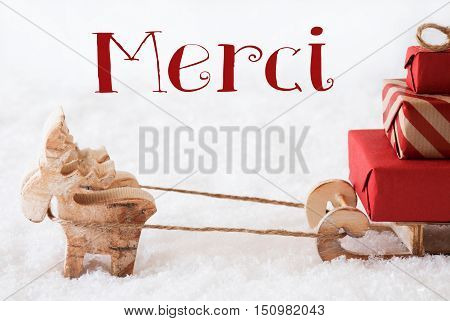 Moose Is Drawing A Sled With Red Gifts Or Presents In Snow. Christmas Card For Seasons Greetings. French Text Merci Means Thank You