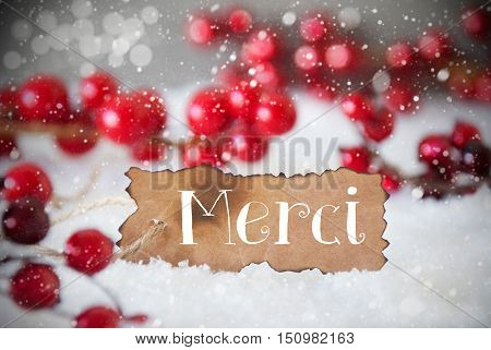 Burnt Label With French Text Merci Means Thank You. Red Christmas Decoration On Snow. Cement Wall As Background With Bokeh Effect And Snowflakes. Card For Seasons Greetings