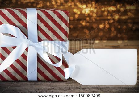 Macro Of Christmas Gift Or Present On Atmospheric Wooden Background. Card For Seasons Greetings, Best Wishes Or Congratulations. White Ribbon With Bow. Label With Copy Space