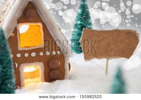 Gingerbread House In Snowy Scenery As Christmas Decoration. Christmas Trees And Candlelight For Romantic Atmosphere. Silver Background With Bokeh Effect. Copy Space For Advertisement
