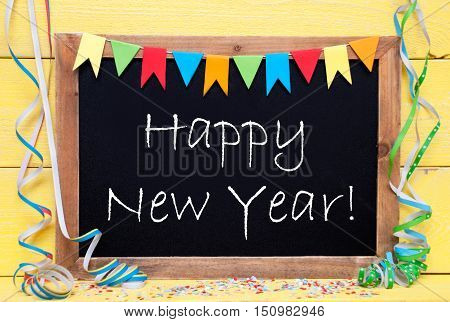 Chalkboard With English Text Happy New Year. Party Decoration Like Streamer, Confetti And Bunting Flags. Yellow Wooden Background With Vintage, Retro Or Rustic Syle