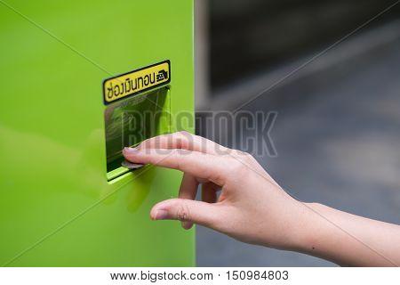 Hand take refund coin on vending machine.