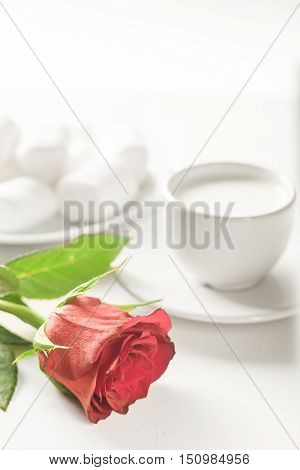 Still life for breakfast in bed captured in low key format with red rose. White on white.