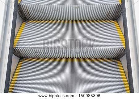 Steps of gray escalator with yellow rim in bright day.