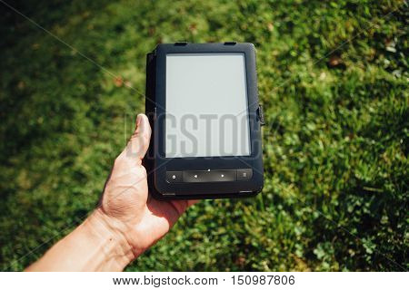e-Book reader in hand, green grass background