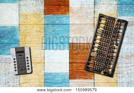 An old chinese abacus and modern calculator on blue wooden background.