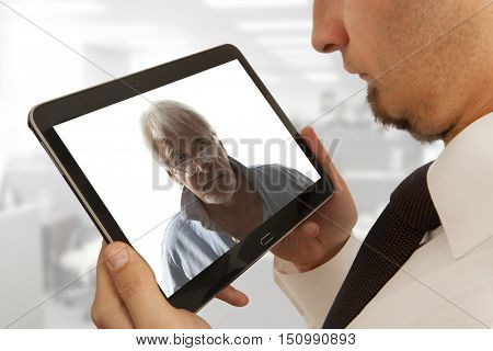 Businessman attending video conference with colleague on digital tablet