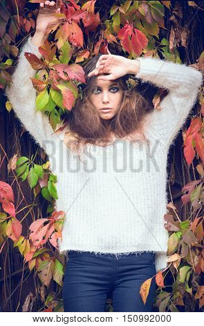 Beautiful girl in autumn leaves. Girl in the hat. Gloomy makeup. Halloween. Fashionable woman. Casual wear. Trend clothing. Toned image.