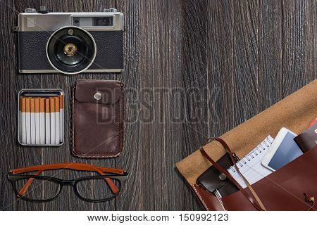 Travel accessories camera eyes glasses phone bag Passport cigarette on black wooden background. Ready for travel