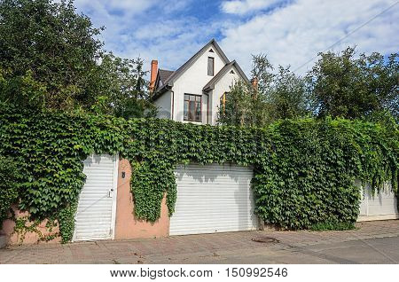Odessa, Ukraine - August 30, 2016: Small white two-storied residential house behind a high fence, overgrown with hops.