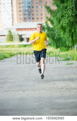 Running man jogging in city street park at beautiful summer day. Sport fitness model caucasian ethnicity training outdoor.