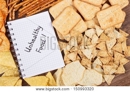 Inscription Unhealthy Food In Notebook And Heap Of Crisps And Cookies