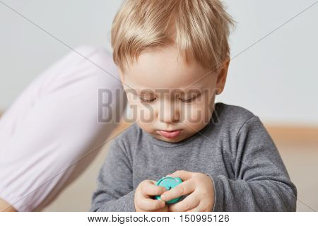 Close-up Shot Of Little Boy Exploring Wristwatches With His Tiny Fingers. Nice Caucasian Toddler Wit