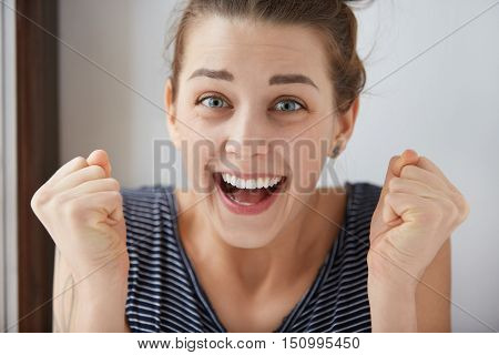Close-up Shot Of Smiling Blue-eyes European Girl Clenching Her Fists In Endless Joy. Positive Emotio