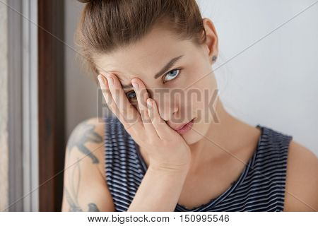 Beautiful Portrait Of Bored Female Resting Half Of Her Face On Her Palm. Attractive Girl With Brown
