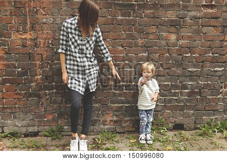 Shot Of Little Boy With His Caring Sister Near Brick Wall. Skinny Caucasian Girl Dressed In Checked
