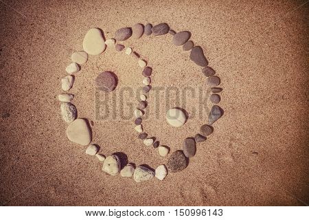 Toned image of Yin Yang symbol in stones on beach sand