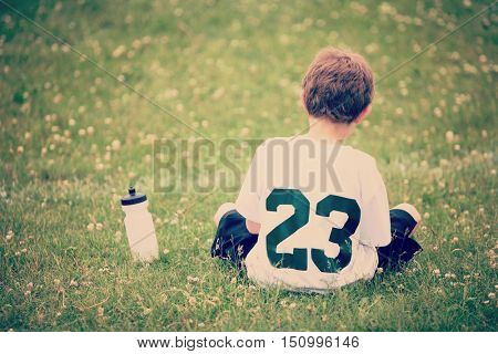 Boy sitting on sidelines with water bottle