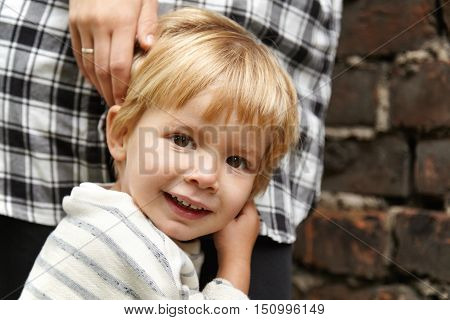 Portrait Of Happy Child Walking With Mommy In The Street. Smiling Male Kid With Brown Eyes, Blond Ha