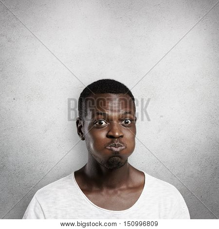 Body Language Concept. Young Dark-skinned Man Puffing Cheeks, Trying Hard To Hold His Breath, Nearly