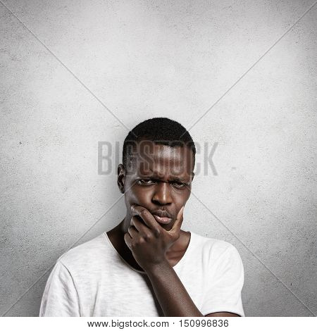 Headshot Of Serious Puzzled African Man Touching His Chin, Looking Thoughtful And Skeptical About So