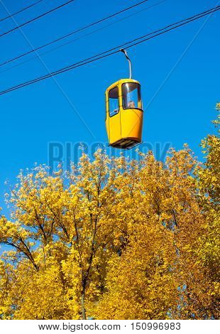 cableway with multicolored cabins in the autumn forest