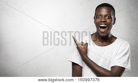 Headshot Of Attractive African Man Looking At Camera With Amazed Expression And Full Disbelief, Poin