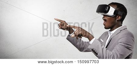 Headshot Of Excited Dark-skinned Businessman Experiencing Virtual Reality, Using 3D Headset Gesturin