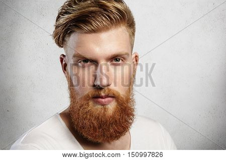 Portrait Of Young Bearded Dandy With Hair Brushed Back In A Trendy Manner. Attractive Caucasian Man