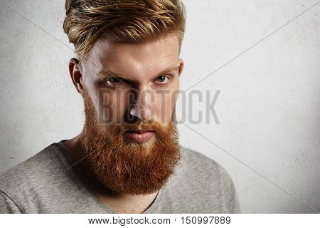 Young Handsome And Brave Man Looking At Camera From Under His Blond Eyebrows. European Hipster In Gr