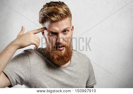 Young Caucasian Macho Man With Blond Beard And Hipster Hair-style Pointing Finger At His Temple Mean