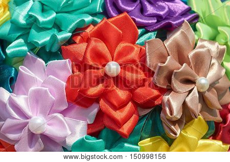 Homemade artificial colored flowers close up as background