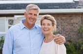 Portrait of a happy senior couple smiling in front of their house. Older couple embracing and lookin poster