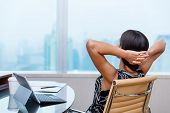 Business woman relaxing working at office desk laid back resting on chair with hands behind head. Wo poster