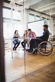 Businessman on wheelchair with photo editors in meeting room at creative office poster