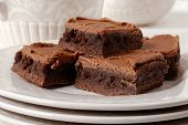 Chocolate frosted brownies on a ceramic plate with matching pitcher and dish in the background.  Sha