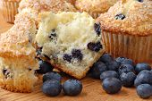Freshly baked blueberry muffin split in half with additional muffins in the background and extra ber