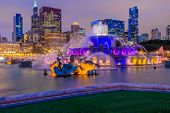 Chicago skyline panorama with skyscrapers and Buckingham fountain in Grant Park at night lit by colo poster