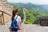 Great Wall of China. Tourist on Asia travel looking at Chinese landscape sitting relaxing on famous  poster
