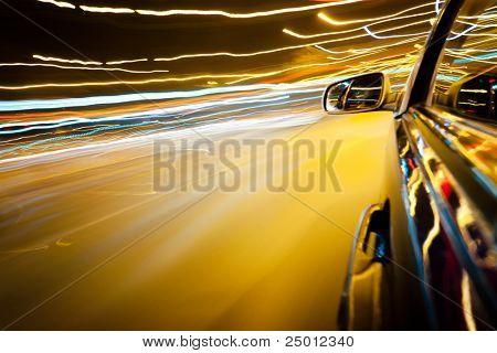 Night traffic,shoot from the window of rush car,motion blur street light.