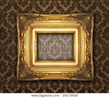 Ornamental gold frame on a damask wallpaper